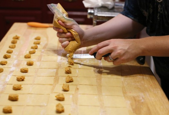 piping out tortellini filling